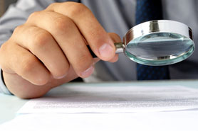 Businessman Looking At Documents Through A Magnifying Glasss