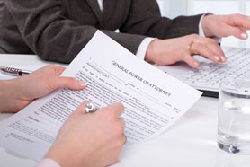 Woman Signing Power Of Attorney Document