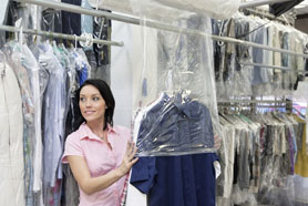 Happy Young Woman Looking Away While Putting Clothes In Plastic